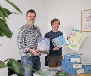 Martin Schinke, dienstältester Mitarbeiter, und Tim Loppe stöbern in alten NATURSTROM-Unterlagen © NATURSTROM AG