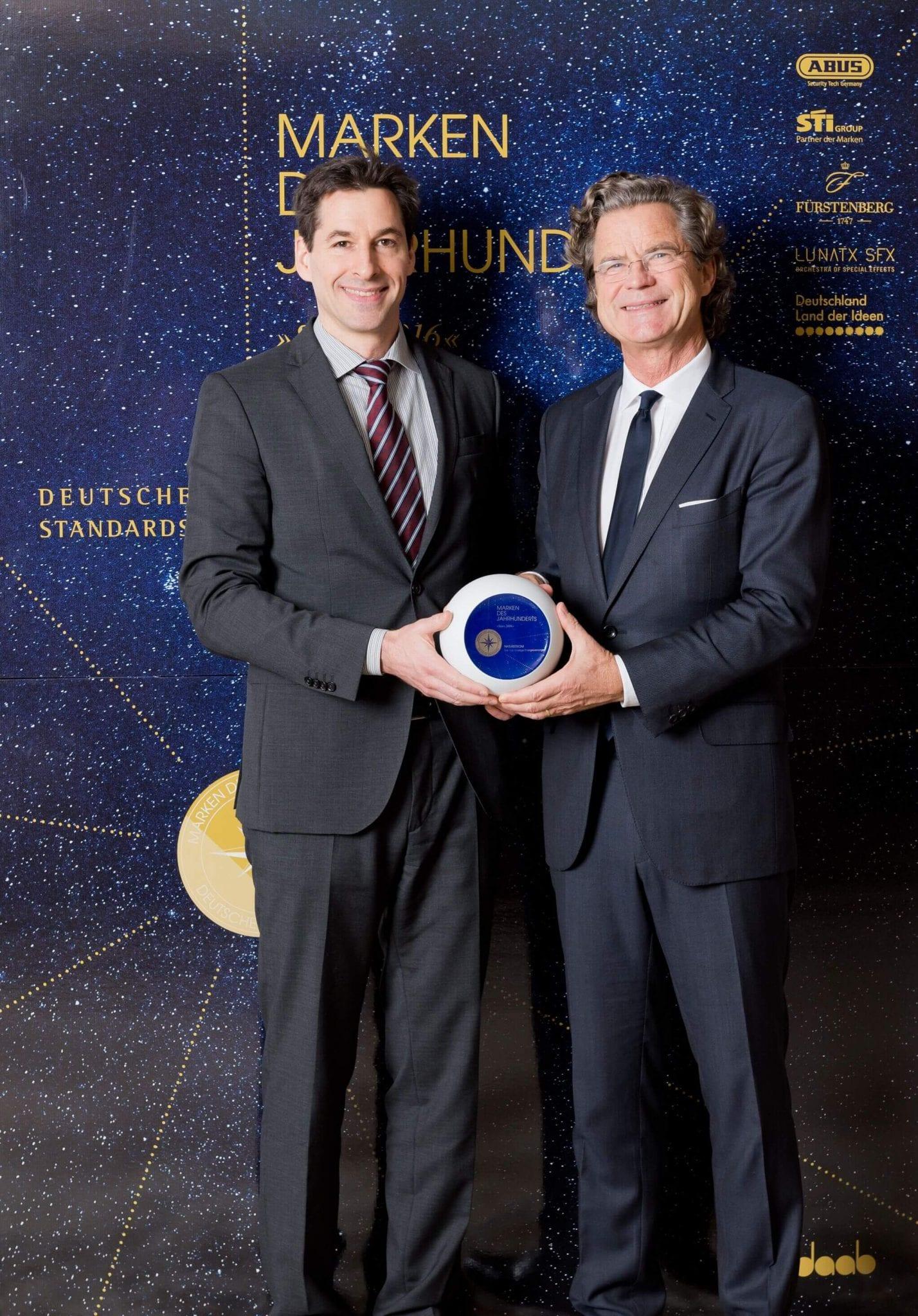 """NATURSTROM-Marketingleiter Dr. Ernst Raupach (links) nimmt den Preis für die """"Marke des Jahrhunderts"""" entgegen. © Deutsche Standards/pjk-atelier"""