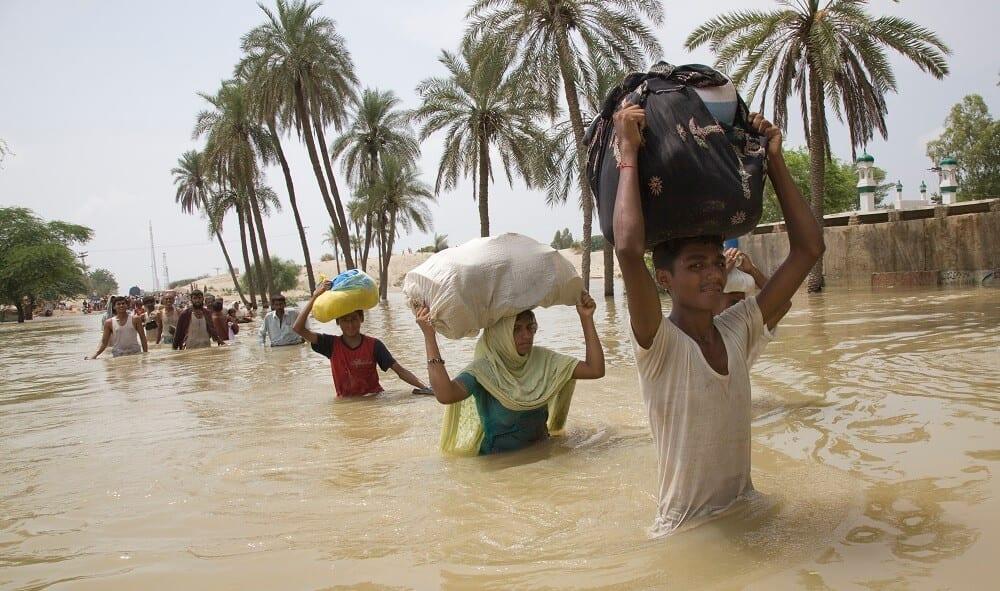 Familien kaempfen sich mit Hab und Gut durch die Wassermassen auf der Suche nach trockenem Boden unter den Fuessen. © Bottelli/Welthungerhilfe