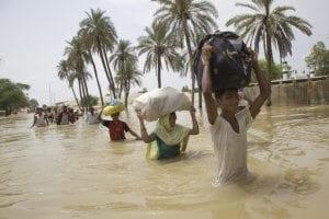 Familien kämpfen sich bei den Überschwemmungen 2010 in Pakistan mit Hab und Gut durch die Wassermassen auf der Suche nach trockenem Boden unter den Füssen. Naturkatastrophen wie die in Pakistan können zu Hunger führen. © Bottelli