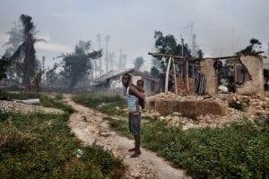 Jeremie steht mit seiner Tochter vor den Ruinen eines Hauses in Grand Anse (Haiti), das Hurrikan Matthew 2016 zerstört hat. Wetterextreme können zu Hungers-Not führen. © Lanfranchi/ Welthungerhilfe