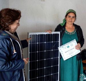 Frau mit Photovoltaikmodul. Foto: Welthungerhilfe